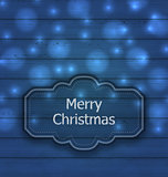 Christmas label on wooden texture with light