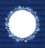 Christmas round frame made in snowflakes on blue wooden backgrou