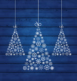 Holiday wooden background with Christmas pines made of snowflake