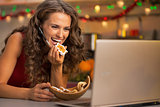 Happy young woman with christmas cookies having video chat on la