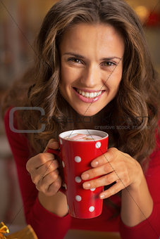 Portrait of happy young woman with cup of hot chocolate