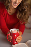 Closeup on young woman with cup of hot chocolate and book