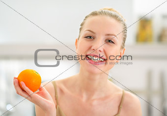 Portrait of happy young woman holding orange