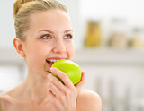 Portrait of happy young woman eating apple