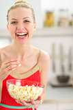 Portrait of happy young woman eating popcorn in kitchen