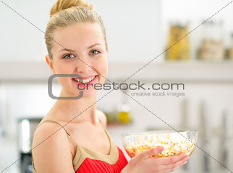 Portrait of happy young woman with popcorn