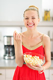 Portrait of smiling young woman eating popcorn in kitchen