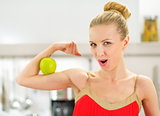 Young woman showing strength of healthy eating