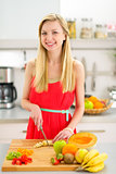 Portrait of happy young woman cutting fruits in kitchen