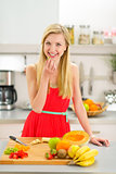 Happy young woman making fruits salad