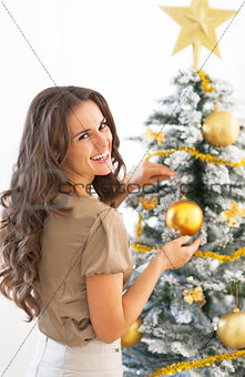 Portrait of smiling young woman decorating christmas tree