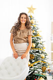 Portrait of smiling young woman standing near christmas tree