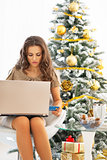 Young woman making online shopping while sitting near christmas