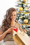 Young woman with christmas present box near christmas tree
