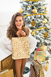 Portrait of happy young woman with shopping bags near christmas