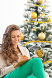 Smiling young woman writing in christmas postcard near christmas