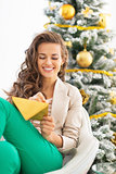 Happy young woman writing christmas letter near christmas tree