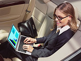 businesswoman in her car with laptop