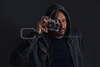 Adult bearded man with dusty camera taking pictures