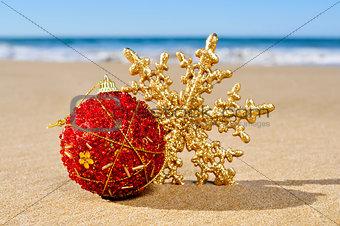 christmas ball and star on the beach