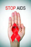 text stop AIDS and a red ribbon in a man hand