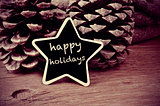 text happy holidays in a star-shaped blackboard, in black and wh