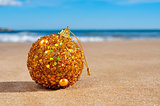 golden christmas ball on the beach