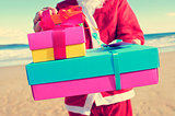 santa claus with gifts on the beach