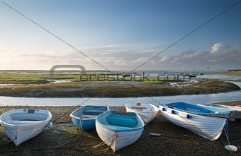 Small leisure boats moored at low tide in marina at Summer sunse