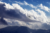 Helicopter in cloudy sky and winter mountains