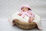 cute baby girl sitting in a basket