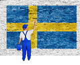 Professional painter covers brick wall with flag of Sweden