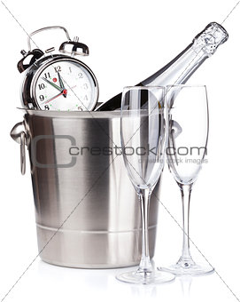 Christmas champagne with alarm clock in bucket and empty glasses
