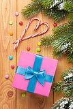 Gift box over christmas wooden background with snow fir tree