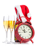 Two champagne glasses, santa hat, bottle and clock