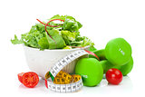 Two green dumbells, tape measure and healthy food