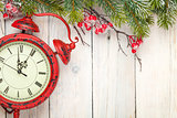 Christmas wooden background with fir tree and antique alarm cloc