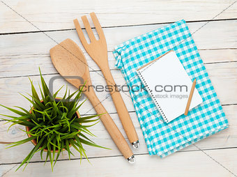 Kitchen utensil and notepad over wooden table