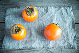 Fresh persimmons on the wooden background