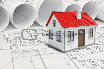 Small model house with red roof near scrolls of architectural drawings