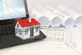 Small model house with red roof on laptop near scrolls of architectural drawings