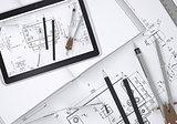 Tablet pc lying on open enpty book and engineering drawings. Tools are close by