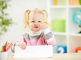Child in eyeglasses drawing picture at home