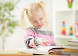 Funny kid in eyeglases reading book at home