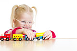 Child in eyeglasses playing toy train isolated