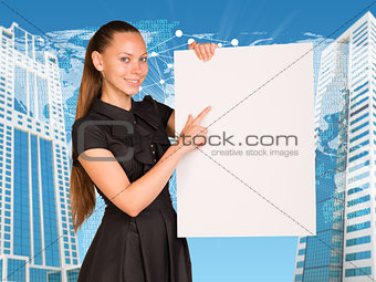 Beautiful businesswoman in dress holding empty paper sheet. Buildings and world map as backdrop