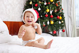 Christmas baby in santa hat sitting on bed and laughing