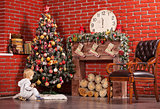 Blonde toddler boy playing near Christmas tree