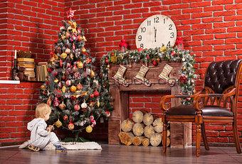Blonde toddler boy playing near Christmas tree