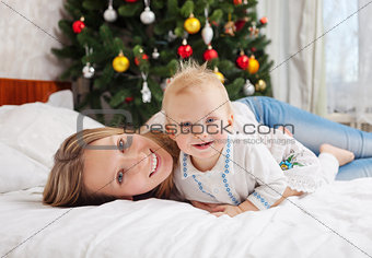 Portrait of happy mother and baby boy on bed at home with decorated Christmas tree in background